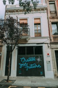"""Graffiti Branding on a garage door reading """"Create Your Future"""" in blue paint"""