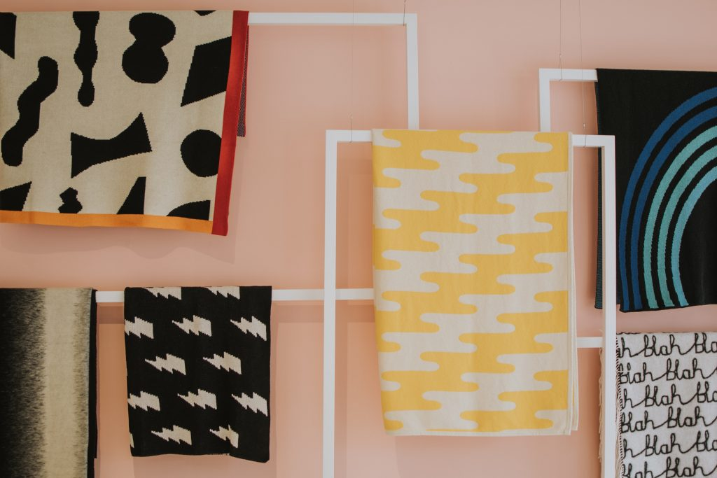 Pieces of brightly coloured cloth curated into geometric wall art as part of creative branding exercise
