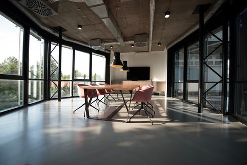 Large meeting room with ceiling high windows and glass partitions inserted as part of office refurbishment